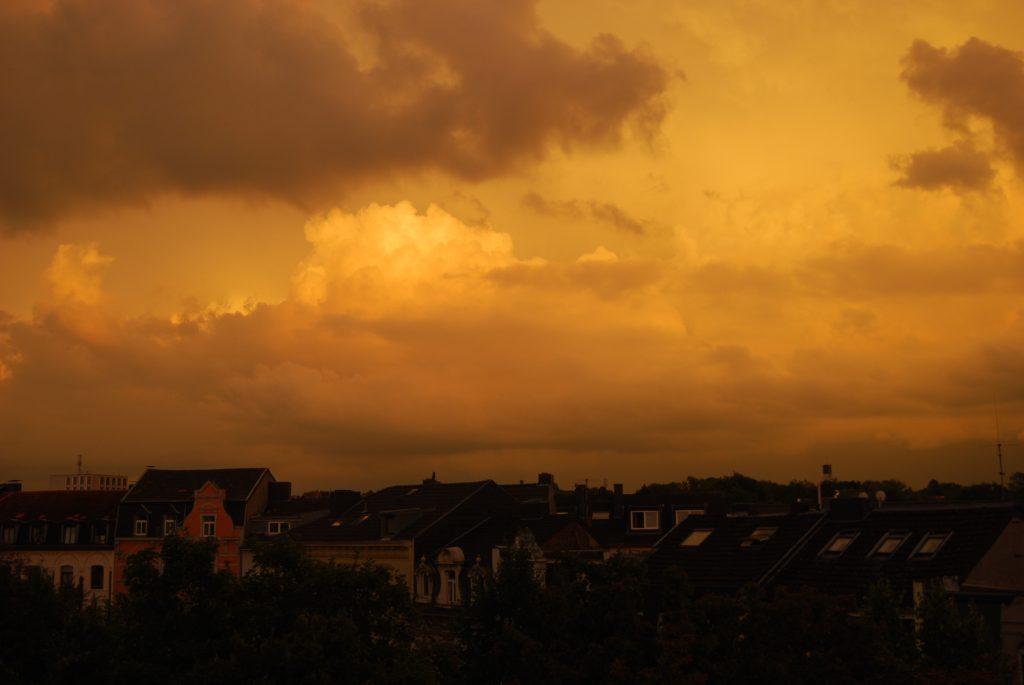 Wolken am orangenen Abendhimmel über einer Stadt